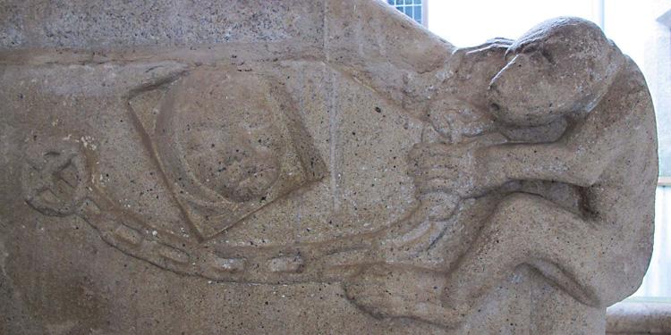Escultura en piedra labrada sobre la escalera interior de la Casa del Mono en Cáceres
